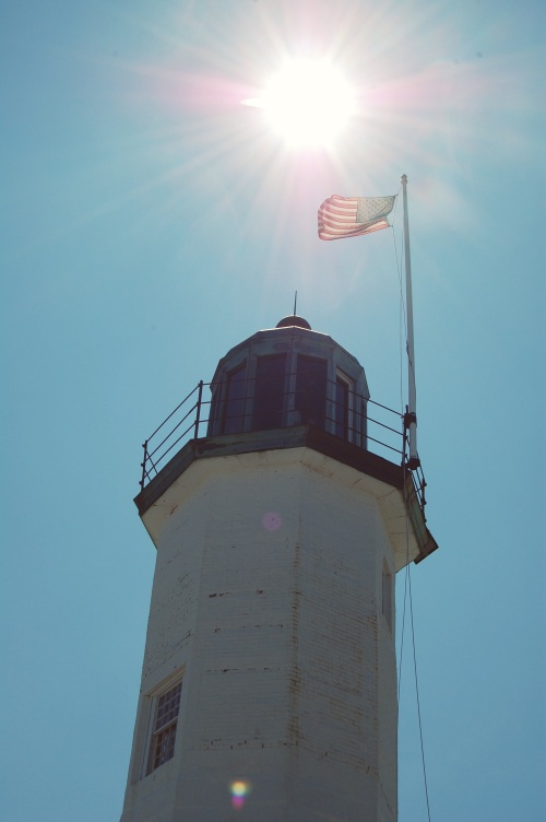 setting sun over lighthouse; old scituate light
